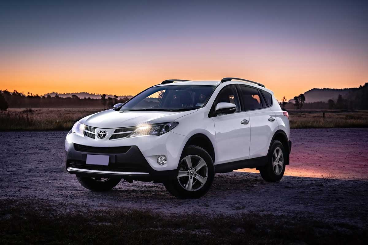 Toyota RAV4 parked in off-road with the view of sunset