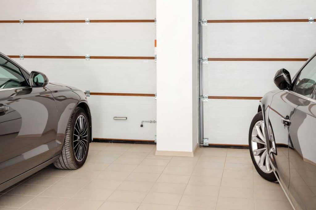 Twi cars inside garage with white roll-up doors