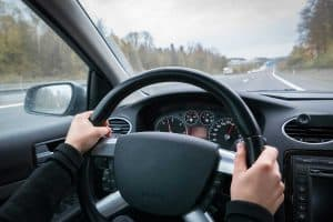 Woman with black sleeves driving on the highway, Steering Wheel Not Straight While Driving [Here's What To Do]