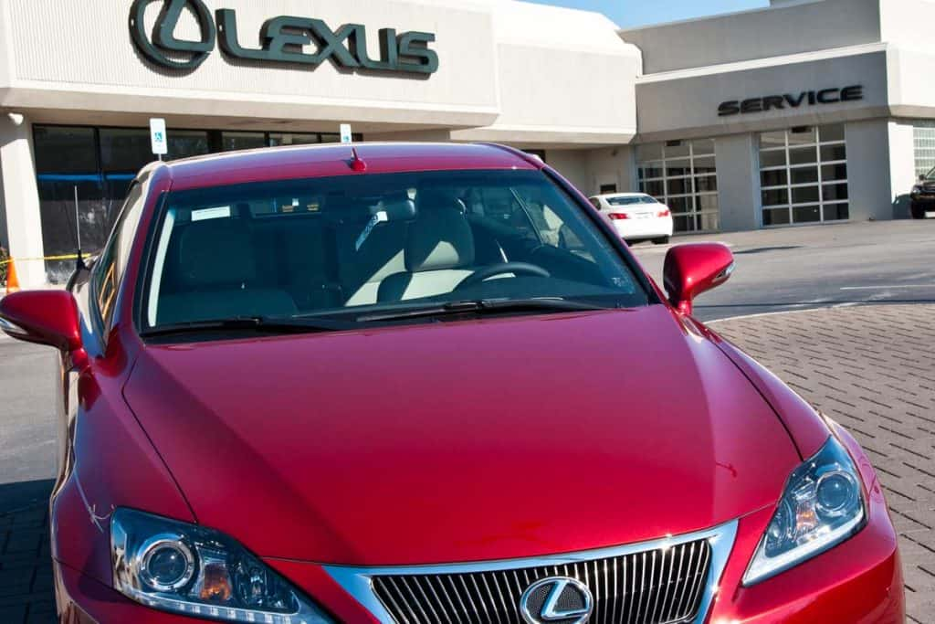Brand new red Lexus in front of a car dealer building, Who Makes Lexus Vehicles?