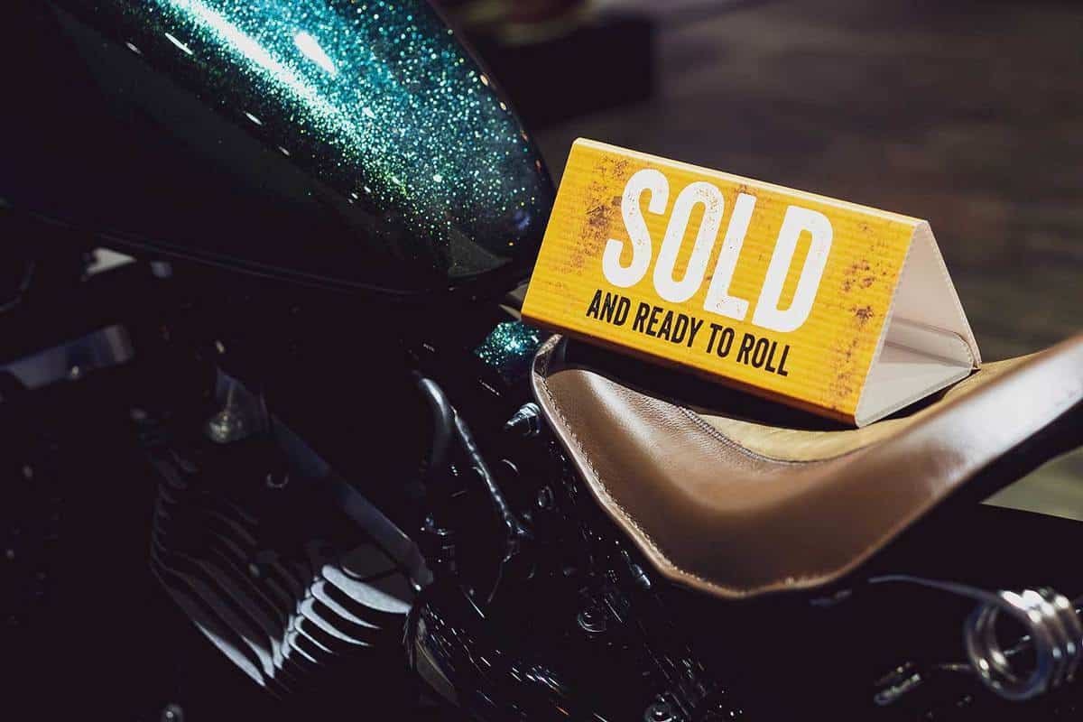 "Close up of Sign ""Sold and Ready to Roll"" on motorcycle"