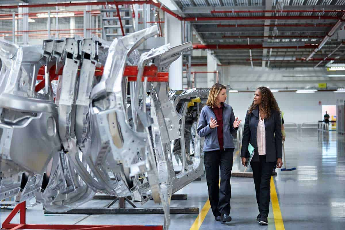 Female engineers discussing by car chassis