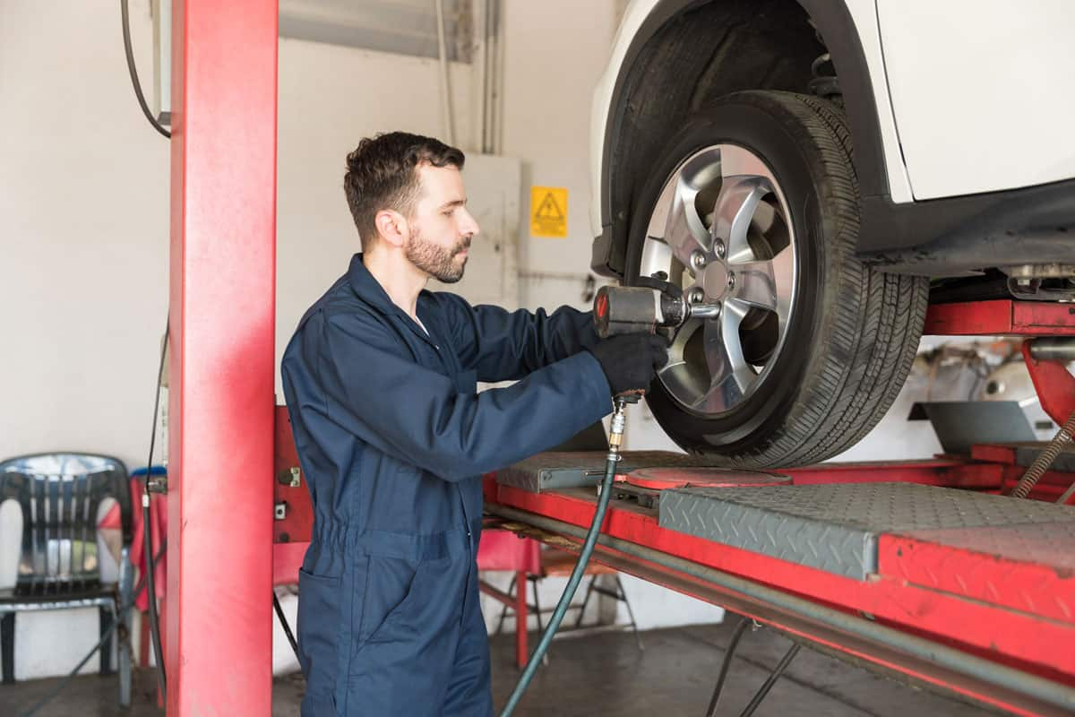 Mechanic attaching back wheels due to misaligned wheels