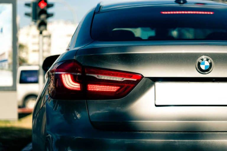 Back of grey BMW X6 car with tail brake light on, Brake Light Comes on When Driving – What Could It Be?