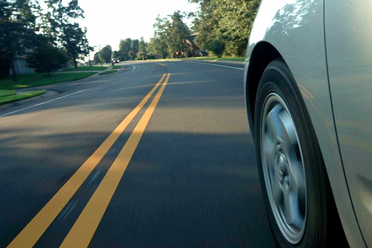 Close up shot of a front wheel driving on the road