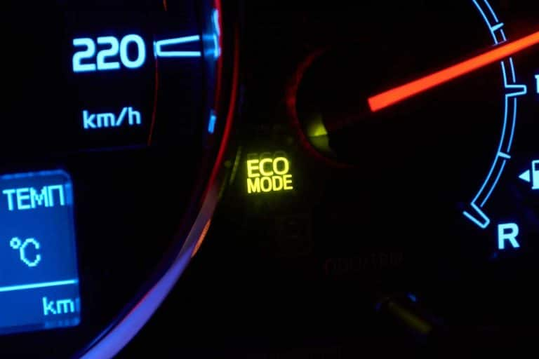 "Close up of car dashboard with green hybrid mode icon on, What Does ""Eco"" On A Car Mean?"