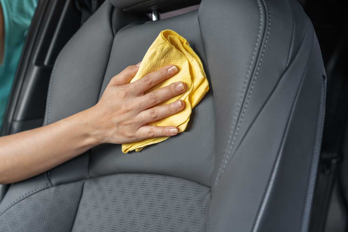 Hand with yellow microfiber cloth cleaning leather seat