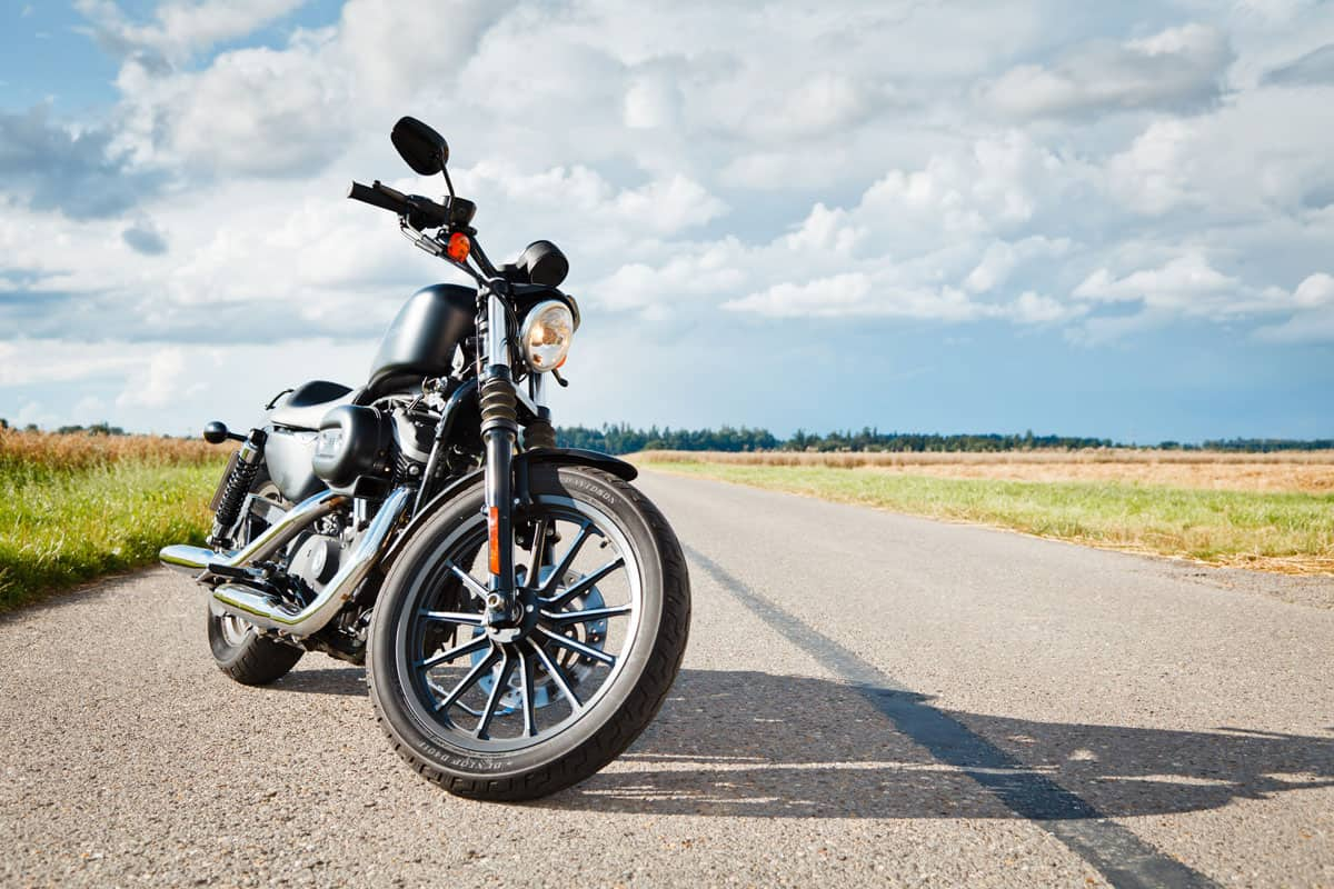 Harley Davidson motorcycle parked on empty road, How Many Miles Can A Motorcycle Last?