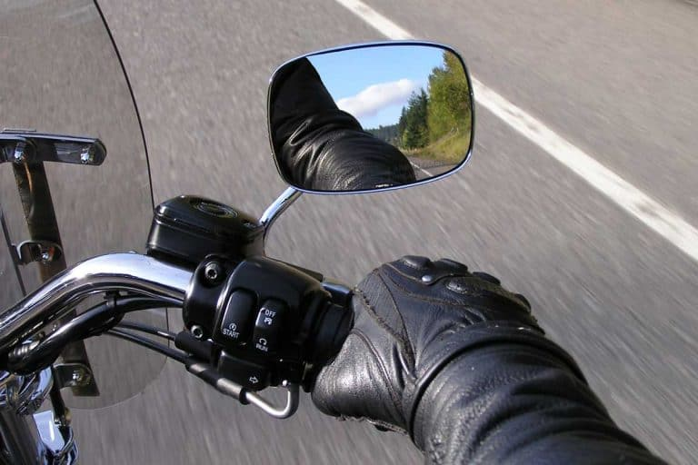 Motorcyclist's hand on throttle with visible beautiful blue sky and greenery in motorcycle side-mirror, Do Motorcycles Need Mirrors?