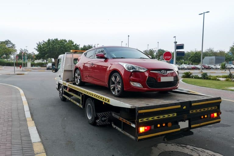Tow truck carrying sedan due to parking violations, What Happens When Your Car Gets Towed?