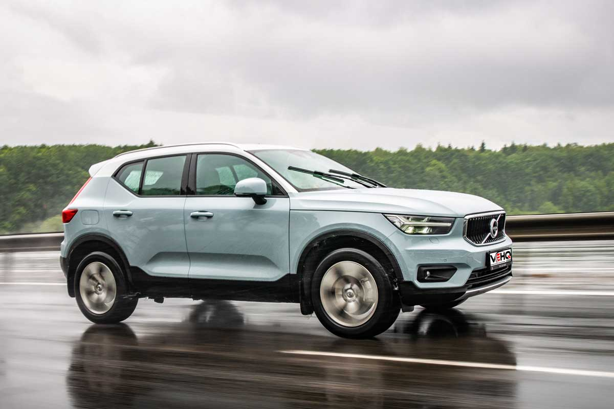 Volvo XC40 drives on a highway during rainy summer day.