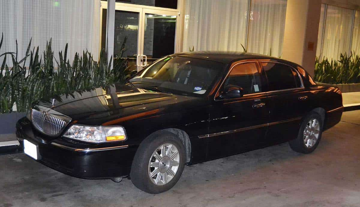 Black Lincoln Town Car parked outside a building