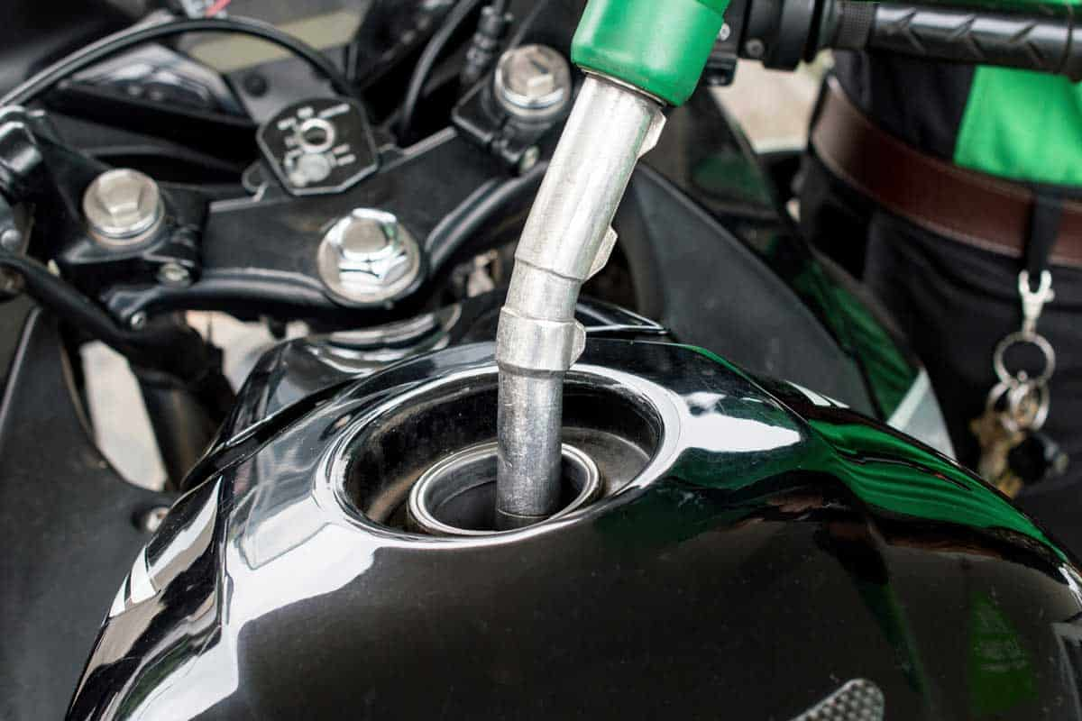 Close-up of someone refilling gas to the motorcycle barrel tank in gas petrol station