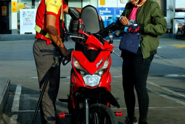 Gasoline station employee refills the fuel tank of a motorcycle for a customer, Do Motorcycles Take Regular Gas?