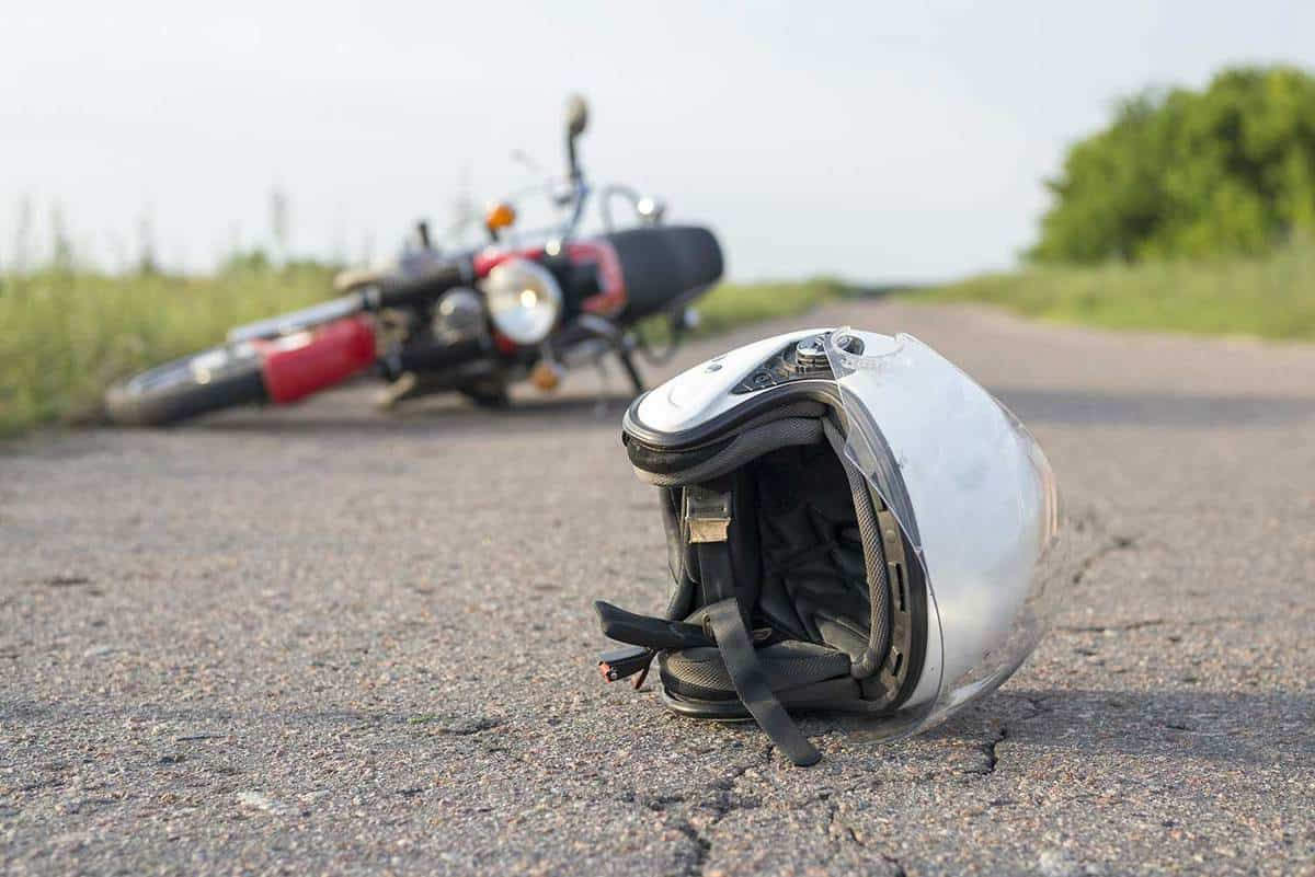 Helmet and motorcycle on road, the concept of road accidents