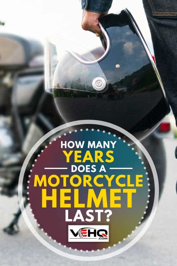 Rider holding a helmet with his motorcycle blurred on the background, How Many Years Does a Motorcycle Helmet Last?