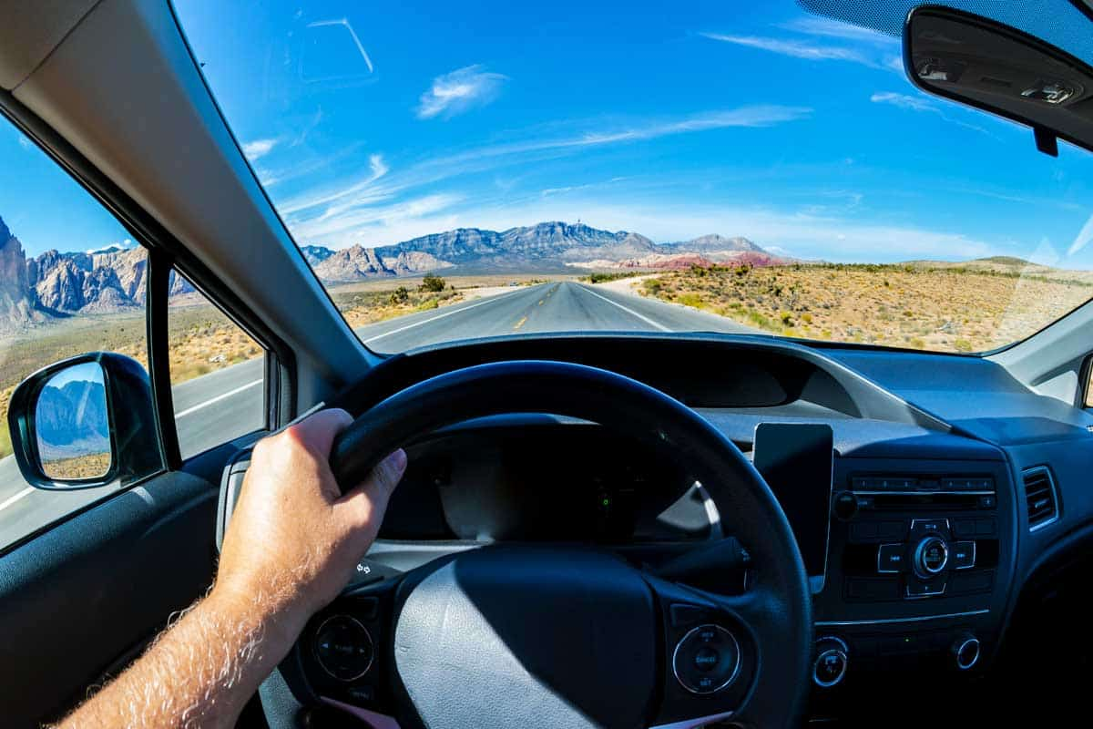 Photo taken inside a car at a beautiful road. A hand holding a steering wheel.