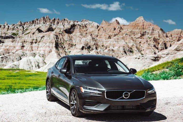View of the new Volvo S60 T6 coupe parked on the road with the Badlands National Park in the background, What Are Foreign Cars? [Inc. Examples]