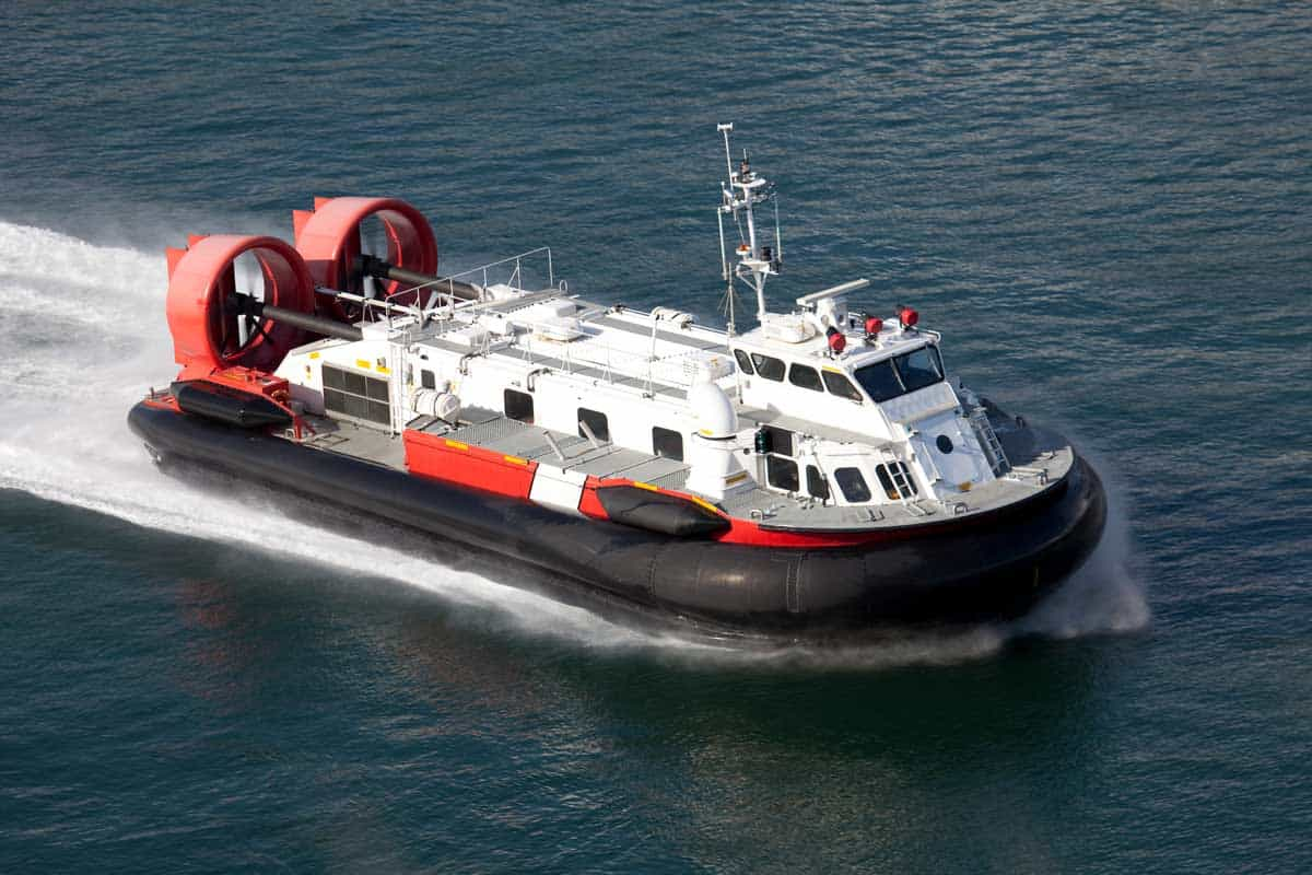 A coast guard hover craft travelling at a high rate of speed.