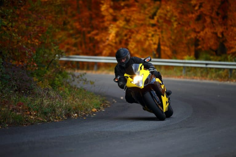 A rider driving his yellow sport bike on the road at autumn, How To Make Your Motorcycle Helmet Quieter?