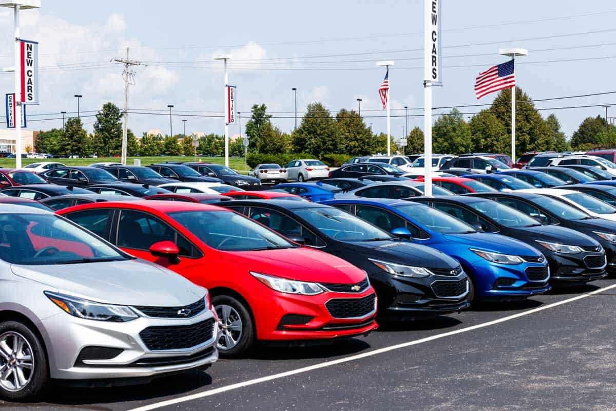 Chevrolet Automobile Dealership with American flag. Chevy is a Division of General Motors, What Is The Best Month To Buy A Car?