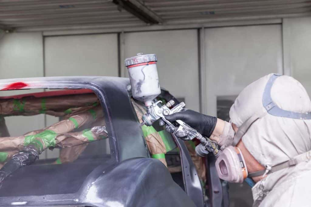 A man in protective overalls and a mask holds a spray bottle in his hand and sprays black paint onto the frame of the car body after an accident during a repair in a vehicle restoration workshop