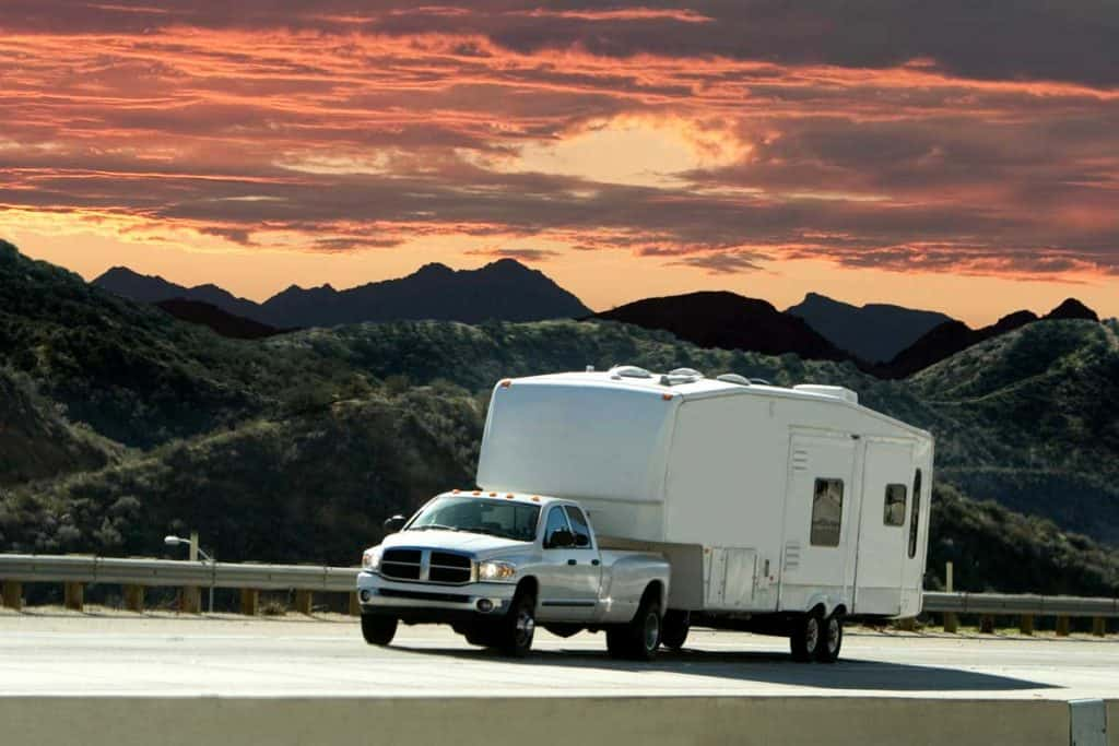 A truck pulling a 5th wheel with a beautiful sunset in the background, What Can My Truck Tow? [Inc. Specs for Popular Models]