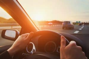 A woman with her hands on the steering wheel and driving on the highway, How To Drive On The Highway Without Fear