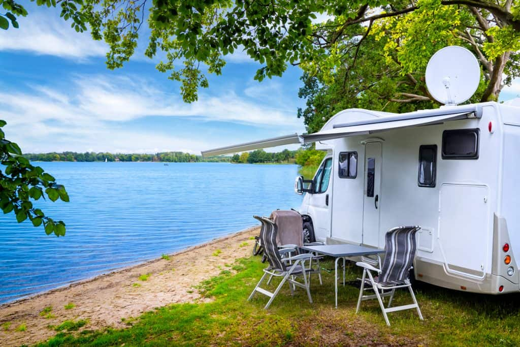 An RV parked on the side of the lake next to a tree for shade, How Much Does RV Camping Cost? [A detailed Analysis with Examples]
