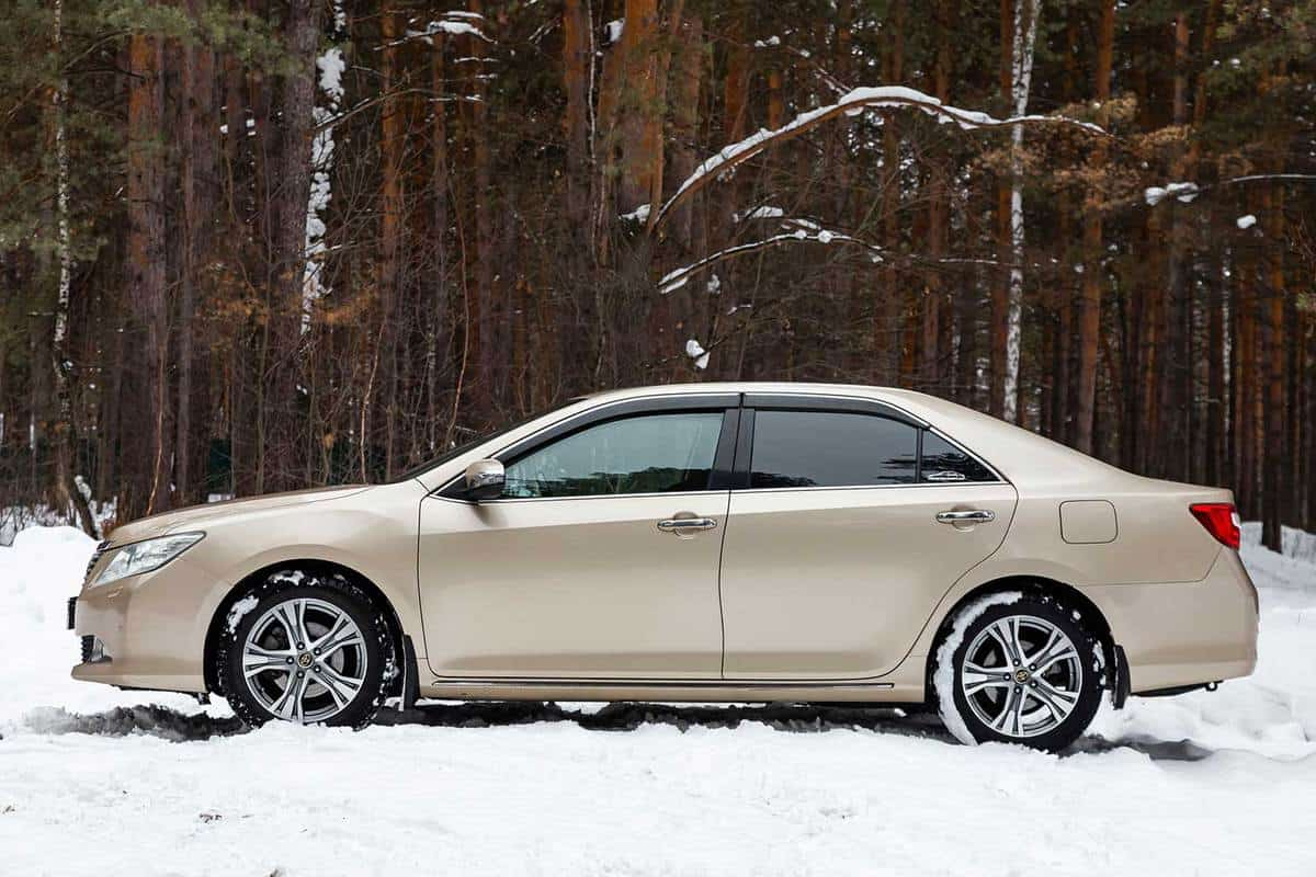 Beige color Toyota Camry on a snowy road
