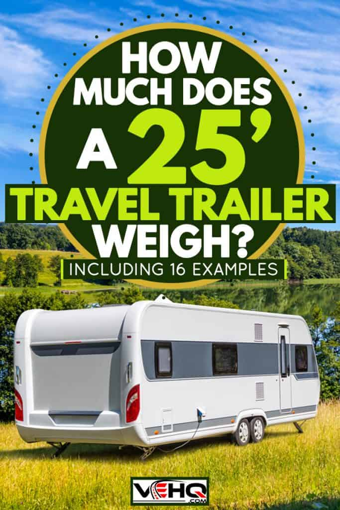 A travel trailer parked on a grassy field with an overview of a lake, How Much Does A 25′ Travel Trailer Weigh? [Inc. 16 examples]