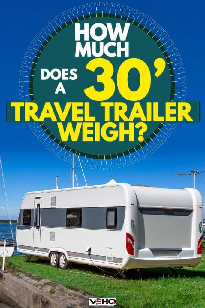 A 30' trailer parked on a dock with a sailboat up front, How Much Does a 30' Travel Trailer Weigh?