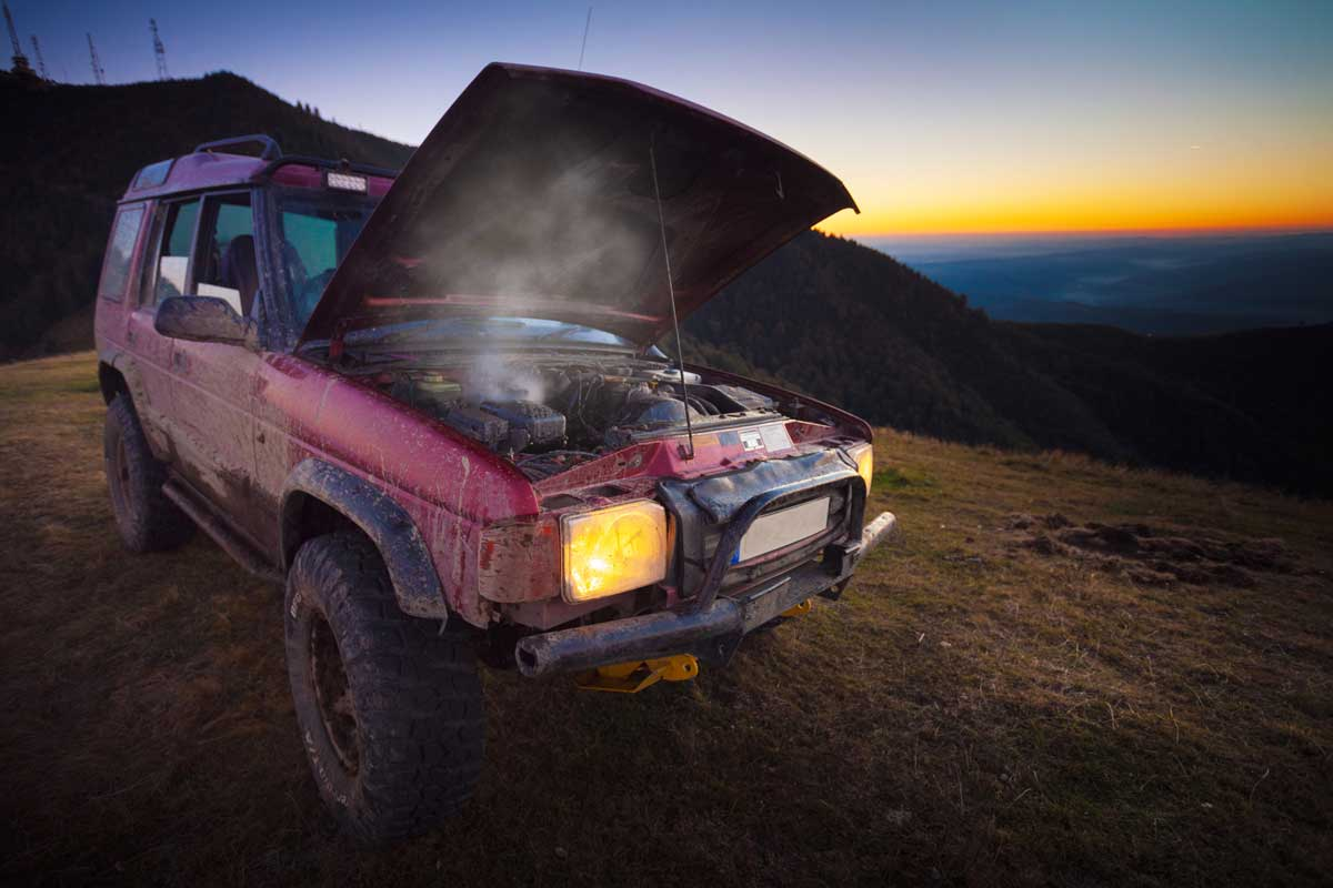 Unrecognisable over heated off-road vehicle broken in the mountains, What Makes A Car Overheat? [5 Common Reasons]