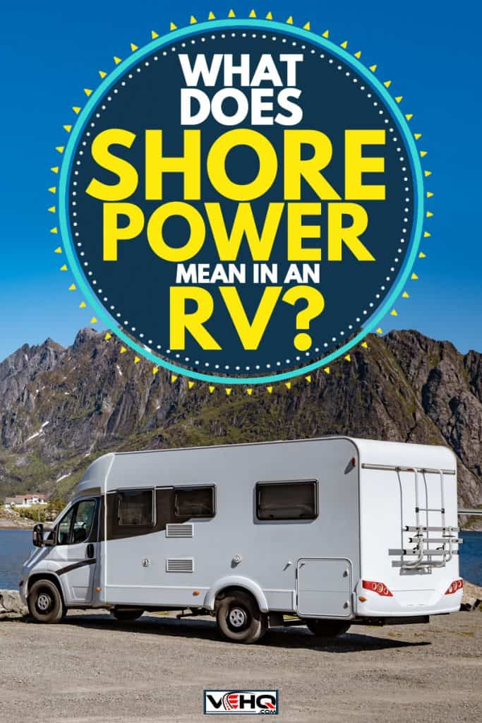 A travel RV parked near a lake with an awesome panoramic mountain range view, What Does Shore Power Mean in an RV?