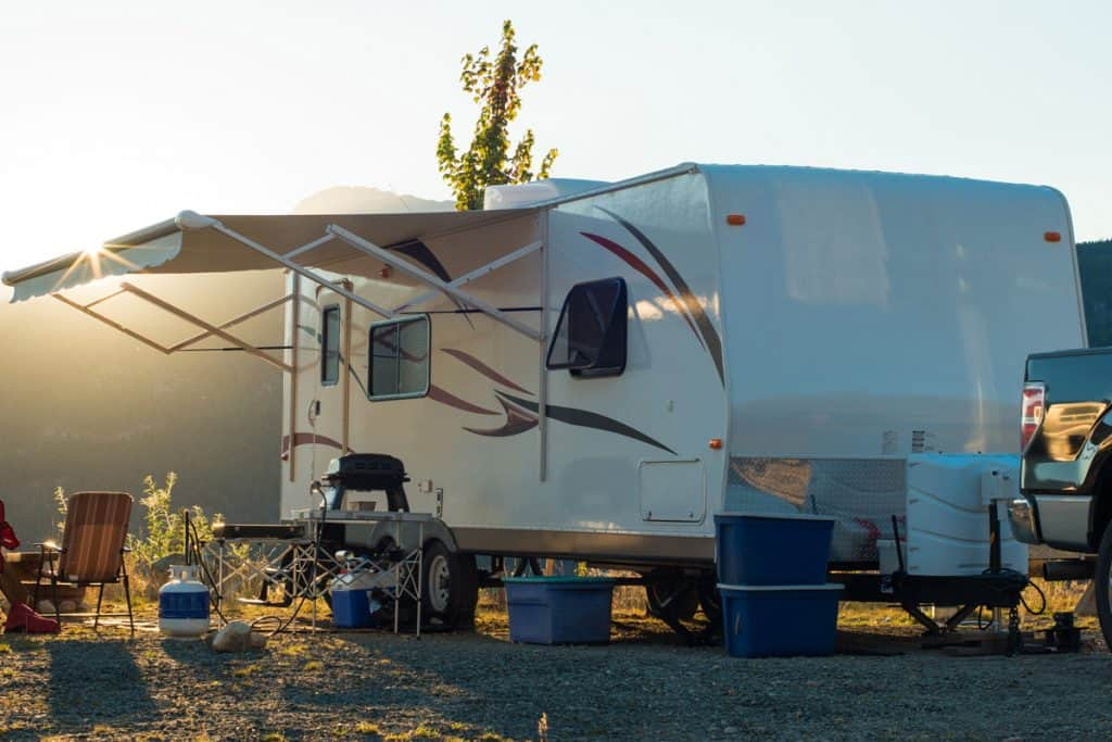 A RV with camping gears set up outside of the car, How to Fix Your RV Roof [Here's What Could Go Wrong]