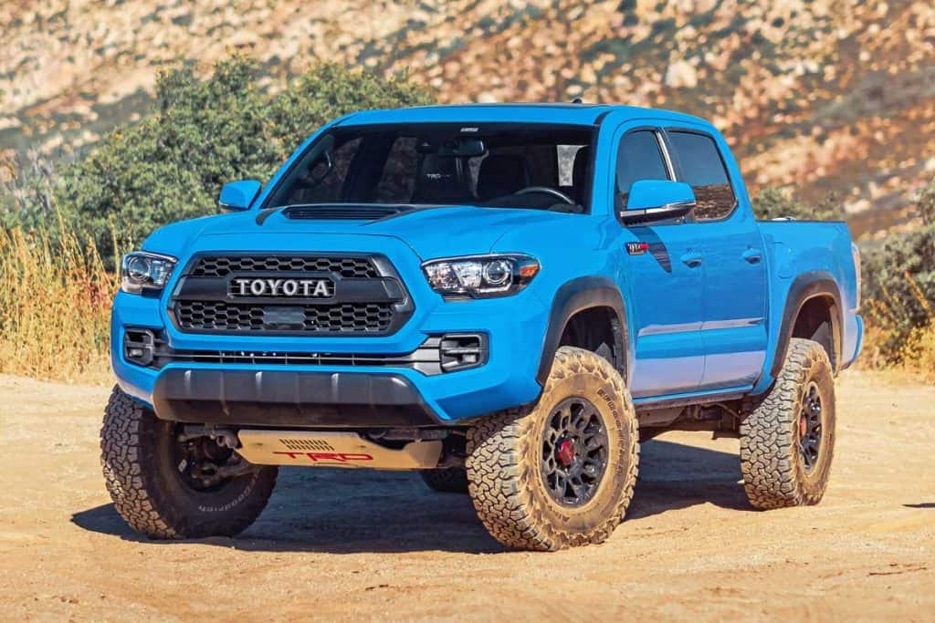 A blue Toyota Tacoma off-roading in the mountains, How Much Legroom Does A Tacoma Truck Have?