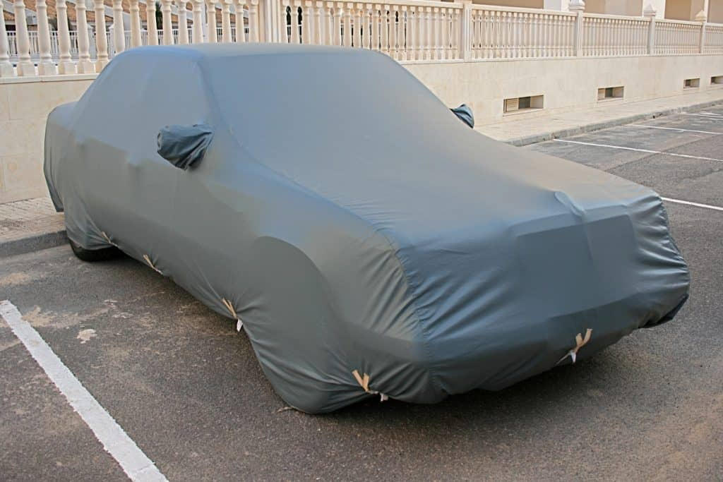 A car with a heat proof cover parked on the side of the street, Do Car Covers Damage Your Car? [Inc. 4 Things You Can Do To Prevent Damage]