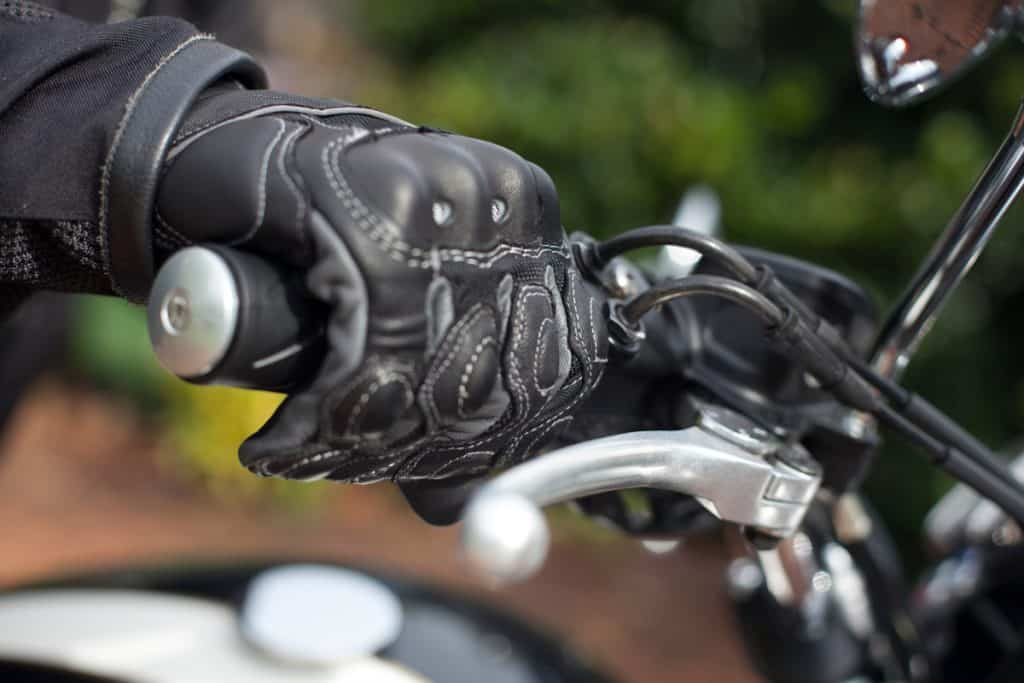 A close up photo of a leather glove of a motorcycle rider, Do Leather Motorcycle Gloves Stretch? [Yes! and Here are 5 ways to do just that!]
