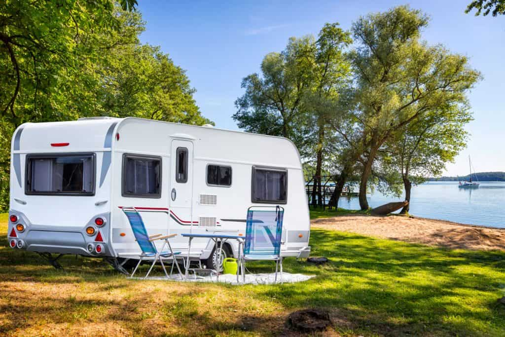 A travel trailer with chairs set up for camping and parked near a lake with a scenic view, Do RV Batteries Charge When Plugged Into Shore Power?