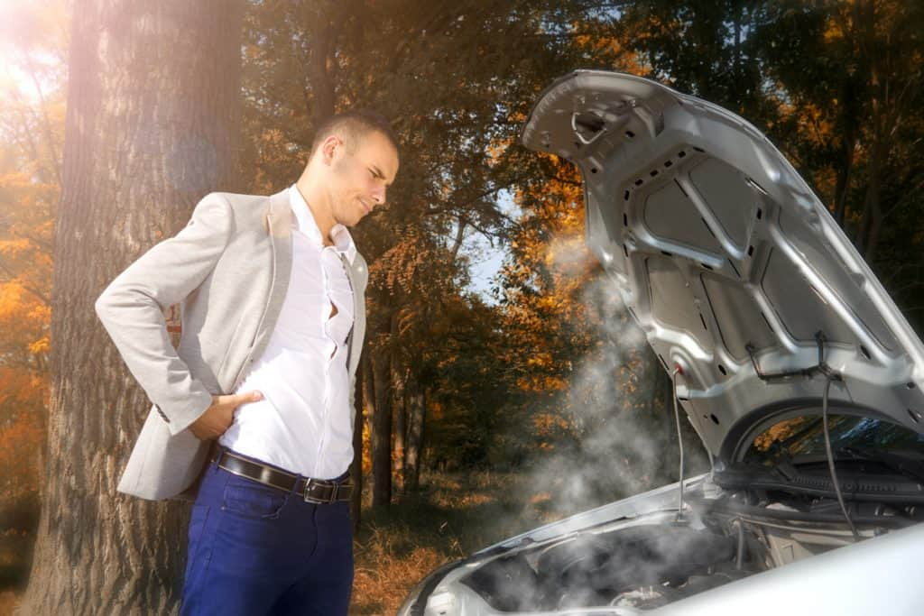 A formally dressed business man checking his car engine because its smoking