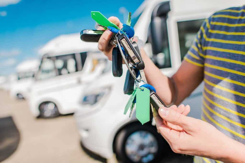 A man's hand holding keys in front of his RVs, How To Replace Your RV Keys [5 Easy Ways]
