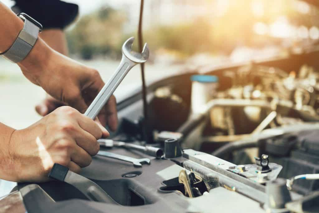 A mechanic holding a wrench and checking the engine for any repairs and in need of maintenance, How Much Does A Car Engine Cost To Replace?