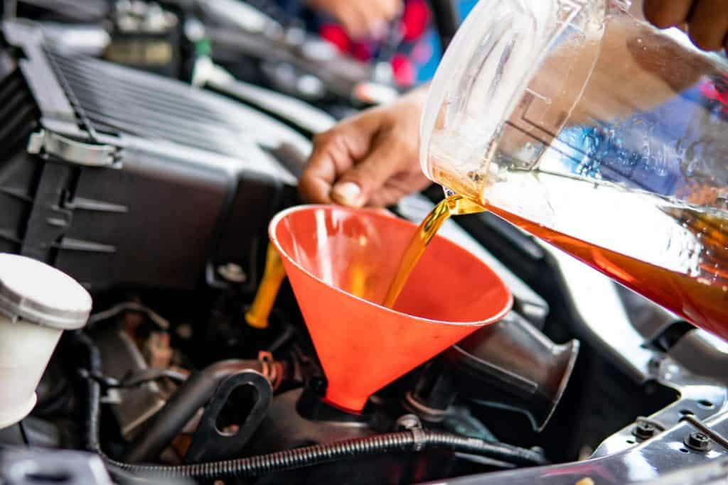 A mechanic pouring oil into the engine of a car, 5 Best Engine Oil Additives For Reducing Engine Noise