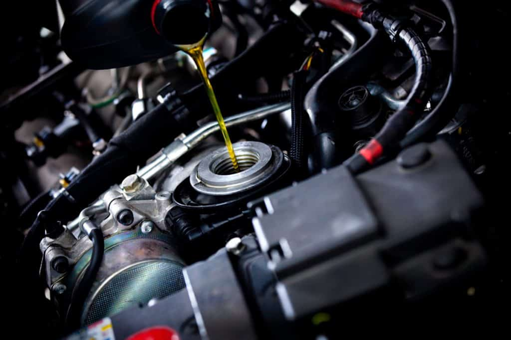 A mechanic pouring oil to the oil intake of the cars engine, 8 Engine Oil Additives that Stop Burning Oil