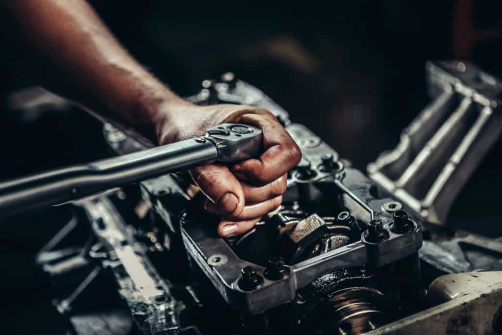 A mechanic using a ratchet in removing an engine part