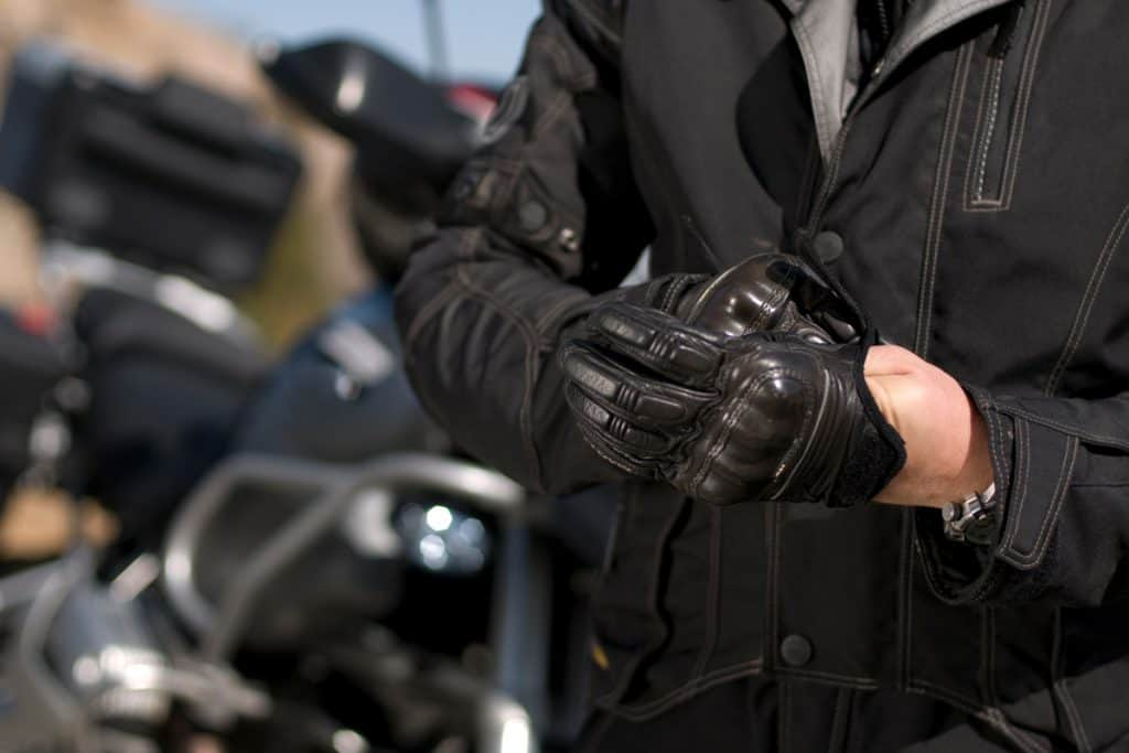 A motorcycle rider putting on his gloves before riding, How Long Do Motorcycle Gloves Last?
