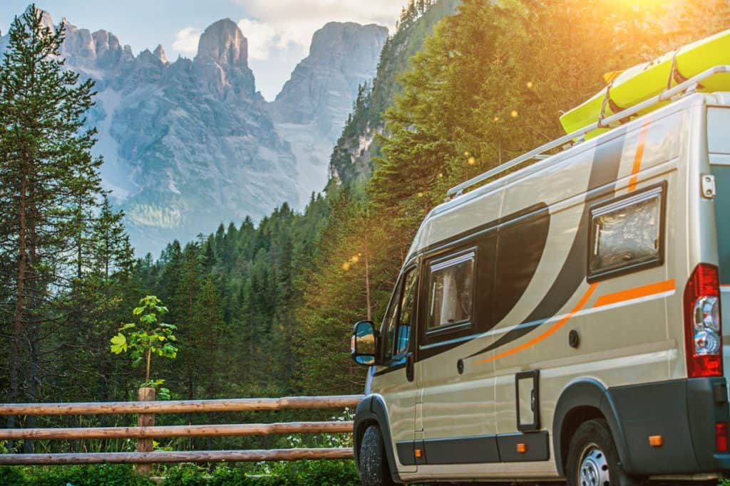 A motorhome parked on a parking lot with a panoramic view of the wild mountains and beautiful skies, What Is The Shortest Class B Motorhome?