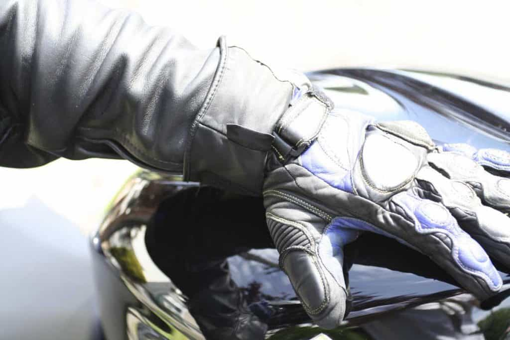 A rider's hand wearing motorcycle leather gloves
