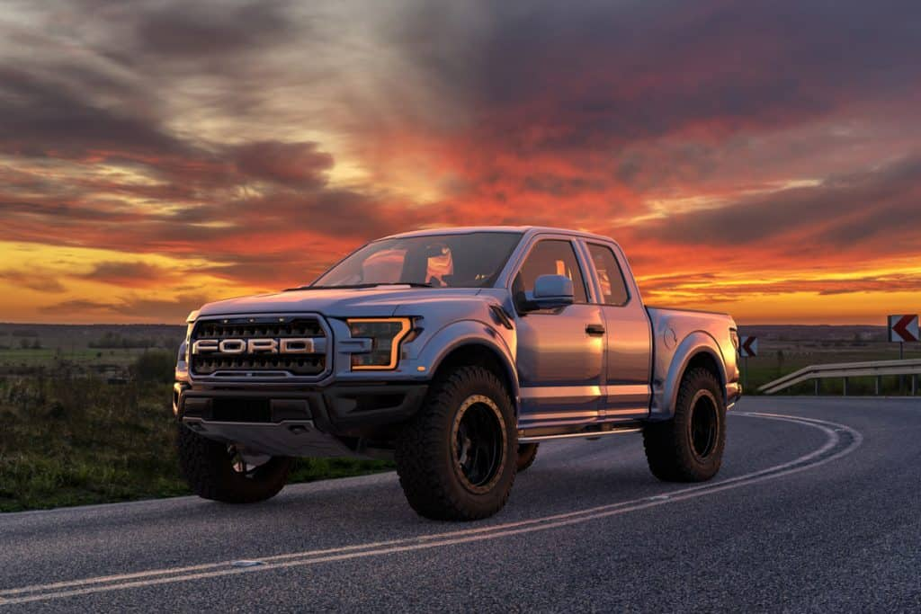 A single cab Ford F-150 Raptor moving down the road at sunset, Why Does My Truck Burn Oil? [And what to do about it]