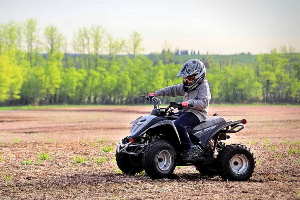 A young man riding youth atv in spring field